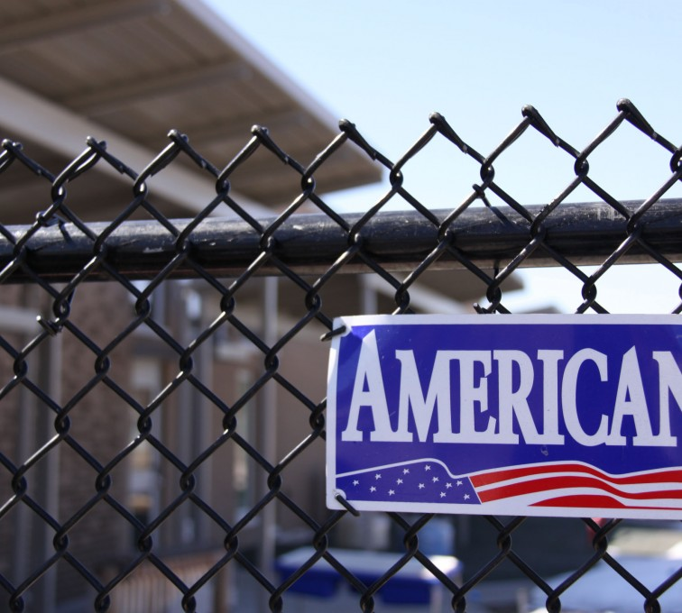 AFC Sioux City - American Fence Company nameplate installed on black vinyl coated chain link fence
