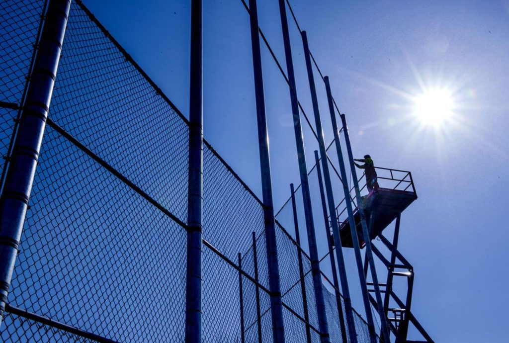 Up on a lift, an American Fence Company employee is installing chain link material on a 40-tall backstop with the backdrop of a cloudless blue sky