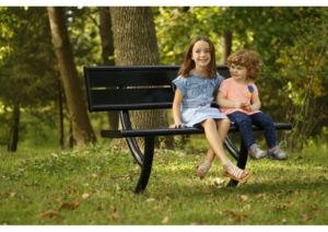 Little girl and little boy smiling and sitting on a park bench