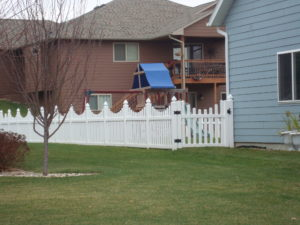 White under arch picket vinyl fence in a residential yard in Sioux City, Iowa