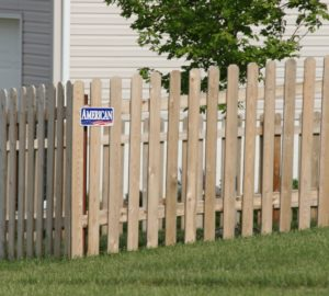 White pine picket fence with an American Fence Company nameplate