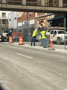 A crew of American Fence Company employees installing temporary construction fence in Sioux City