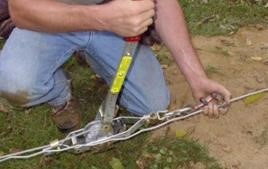 Tightening bottom tension wire on a chain link fence