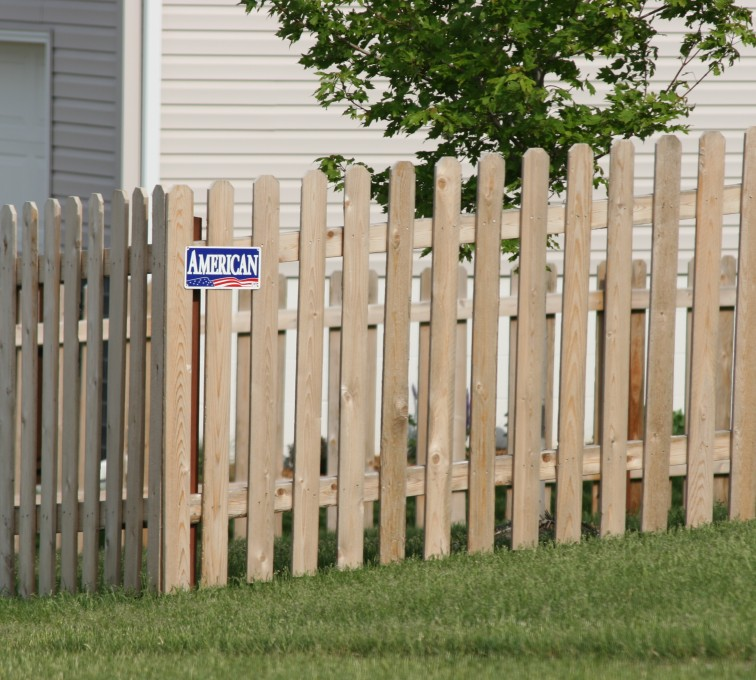 White pine fence with an American Fence Company sign in Sioux City, IA