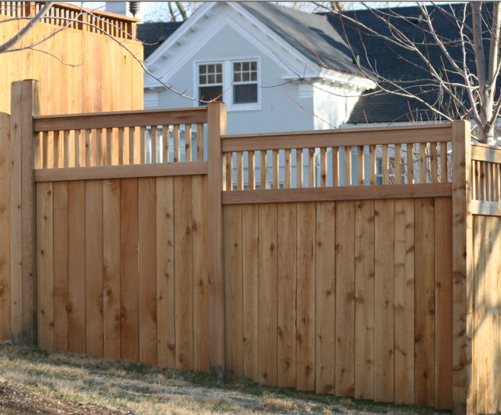 A residential wooden solid fence with top accent